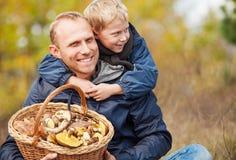 Fadern och sonen är lyckliga att de har funnit en korg mycket av champinjoner royaltyfri fotografi
