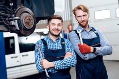 Fadern och sonen arbetar på den auto servicen Två mekaniker arbetar med detaljerna av bilen royaltyfri bild