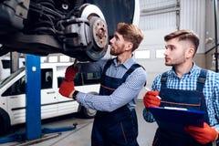 Fadern och sonen arbetar på den auto servicen Två mekaniker arbetar med detaljerna av bilen arkivfoton