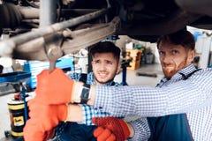 Fadern och sonen arbetar på den auto servicen Två mekaniker arbetar med detaljerna av bilen arkivbilder