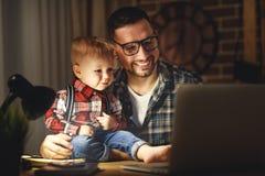 Fadern och sonen behandla som ett barn arbete hemma på datoren i mörker arkivbild