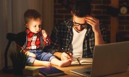 Fadern och sonen behandla som ett barn arbete hemma på datoren i mörker royaltyfria bilder