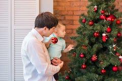 Fadern och sonen dekorerar julgranen royaltyfri bild