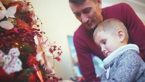 Fadern och sonen dekorerar julgranen tillsammans lager videofilmer