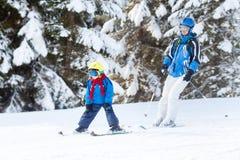 Fadern och sonen, det förskole- barnet som skidar i österrikare, skidar semesterort I Arkivbild