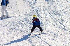 Fadern och sonen, det förskole- barnet som skidar i österrikare, skidar semesterort I Royaltyfria Bilder
