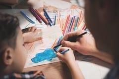 Fadern och sonen drar med färgblyertspennor och markörer på papper på natten hemma royaltyfria bilder