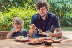 Fadern och sonen försöker indisk mat i ett kafé på gatan royaltyfria bilder