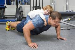 Fadern och sonen gör sportar Arkivbilder
