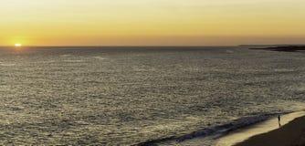 Fadern och sonen håller ögonen på solnedgången på kanten av havet, på stranden fotografering för bildbyråer