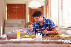 Fadern och sonen har en matställe i restaurang Arkivbild