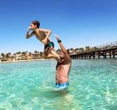 Fadern och sonen har gyckel på havet fotografering för bildbyråer