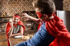 Fadern och sonen i röd superhero kostymerar att äta i kök royaltyfri foto