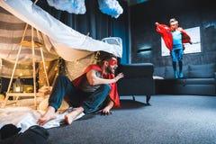 Fadern och sonen i röd superhero kostymerar att spela arkivbild