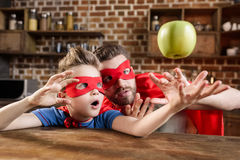 Fadern och sonen i röd superhero kostymerar att spela med äpplet Arkivbilder