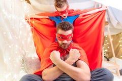Fadern och sonen i superhero kostymerar att spela tillsammans fotografering för bildbyråer