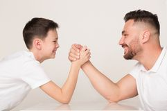 Fadern och sonen konkurrerar i armbrottning arkivfoton
