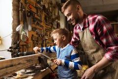 Fadern och sonen med raspar arbete på seminariet Arkivbild