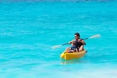 Fadern och sonen på en kajak rider i ett tropiskt hav royaltyfri bild