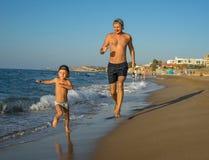 Fadern och sonen på kusten kopplas in i sportar Fadern och hans son kör längs stranden En ung man med hans son är royaltyfri fotografi