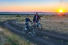 Fadern och sonen rider en cykel i landet på fältet i aftonen Arkivfoton