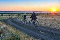 Fadern och sonen rider en cykel i landet på fältet i aftonen Arkivfoto
