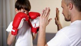 Fadern och sonen som förbereder sig för ask, slåss, sportbarndom, styrka och kurage royaltyfri foto