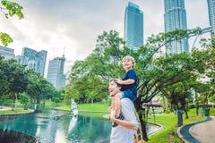 Fadern och sonen som handelsresande i Malaysia mot en bakgrund står högt Patronas, kopplar samman Resa med barnbegrepp Royaltyfri Fotografi