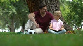 Fadern och sonen som läseboken parkerar in, mannen, uppmuntrar pojken till kunskap, familj lager videofilmer