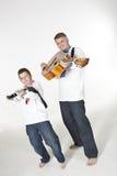 Fadern och sonen som siktar med gitarrer, gillar vapen Royaltyfri Fotografi