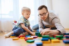 Fadern och sonen som spelar med leksaken, blockerar hemma Royaltyfria Foton