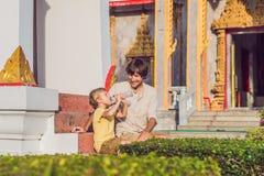 Fadern och sonen som turister ser Wat Chalong, är den viktigaste templet av Phuket arkivfoto