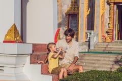 Fadern och sonen som turister ser Wat Chalong, är det mest importan fotografering för bildbyråer