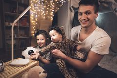Fadern och sonen spelar med lite behandla som ett barn systern på natten hemma royaltyfri foto
