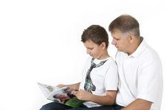 Fadern och sonen studerar tillsammans Arkivbild