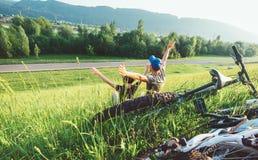 Fadern och sonen vilar tillsammans i gr?nt gr?s, n?r ha cykeln att g? arkivfoton