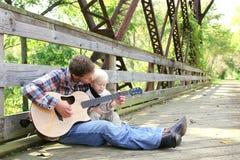 Fadern och unga barnet som spelar gitarren utanför på, parkerar arkivbild