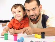 Fadern och ungen som leker med, färgar Arkivfoton