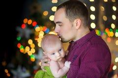 Fadern omfamnar försiktigt den nyfödda sonen Arkivfoto