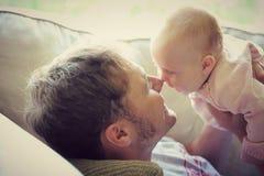 Fadern PLaying med lyckligt behandla som ett barn hemma Royaltyfria Bilder
