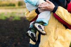 Fadern rymmer behandla som ett barn i hans armar i smutsiga gymnastikskor Arkivbild