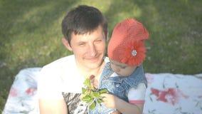 Fadern rymmer hans lilla dotter i hans armar och talar till kameran arkivfilmer
