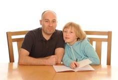 Fader och dotter med läxa arkivbild