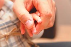 Fadern som rymmer en hand av hans, behandla som ett barn Arkivfoto