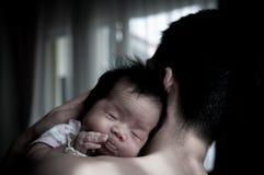 Fadern som rymmer hans nyfött, behandla som ett barn bredvid fönster Efter mjölka från moder, bröstet för ` som s är en naturlig  Royaltyfri Bild