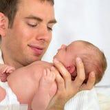 Fadern som rymmer lite fyra veckor gamla, behandla som ett barn. Arkivbilder