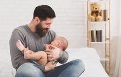 Fadern som rymmer och lugnar att gråta som är nyfött, behandla som ett barn i hans armar royaltyfria foton