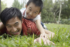 Fadern And Son Lying på gräs på parkerar royaltyfri fotografi