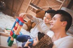 Fadern son och behandla som ett barn lite dottern spelar med kuber för barn på natten hemma arkivbild