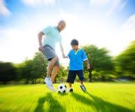 Fadern Son Playing Soccer parkerar sommarbegrepp royaltyfri bild
